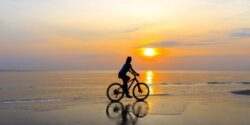woman bike riding on beach