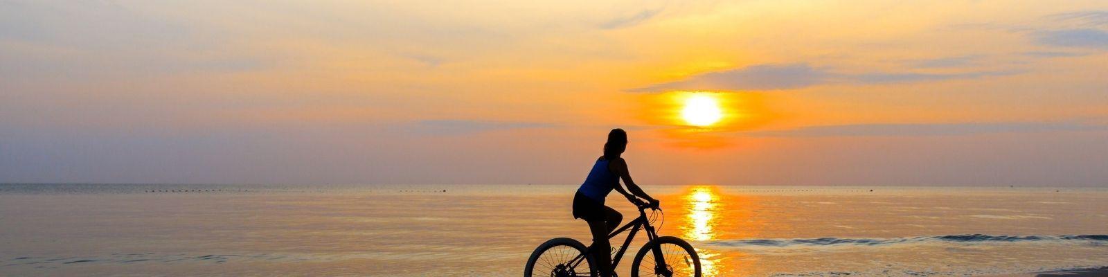 woman biking at sunset
