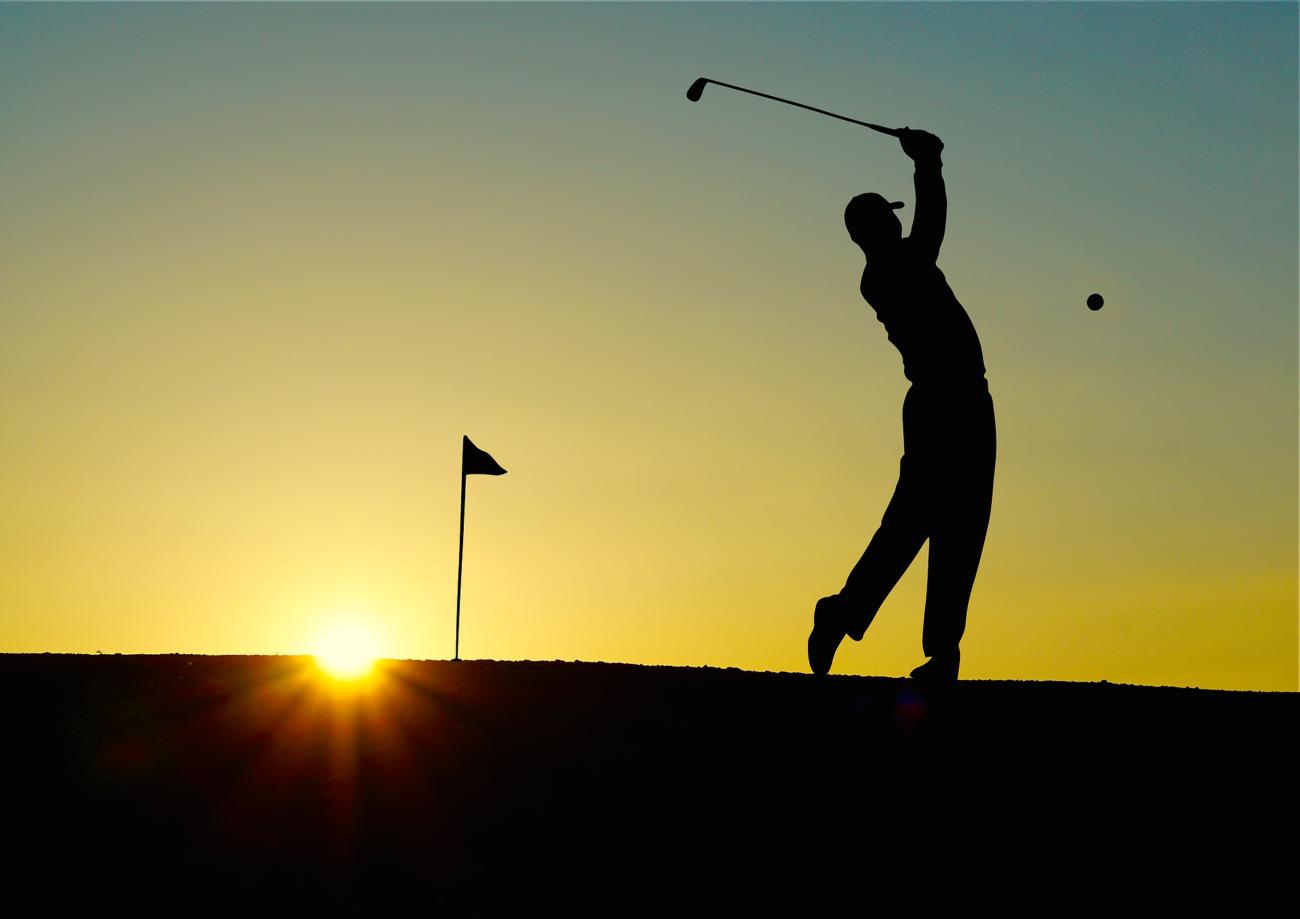 person swinging golf club
