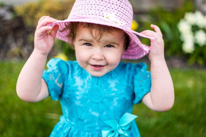 little girl holding her hat