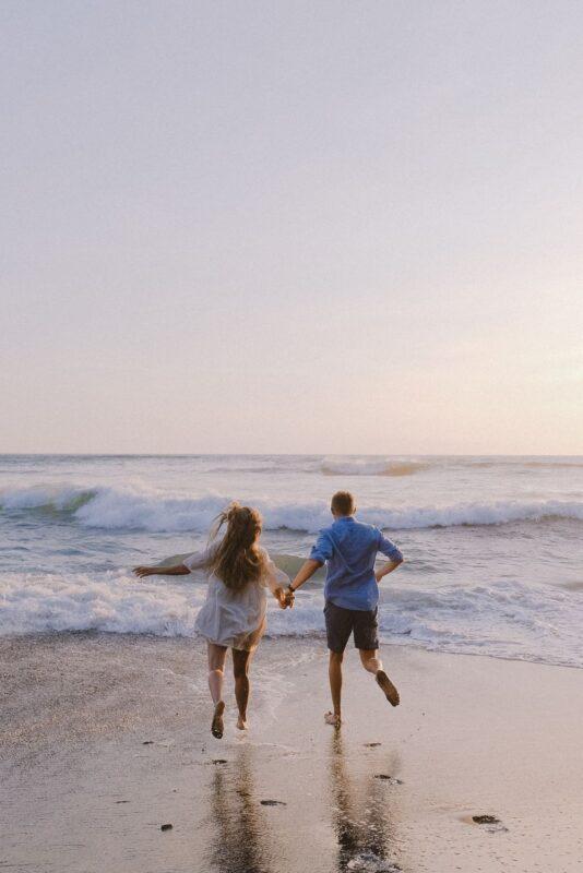 couple running into ocean