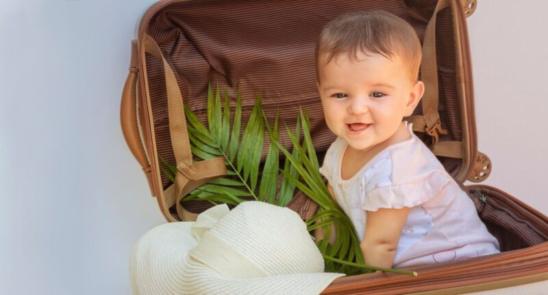 baby in suitcase smiling