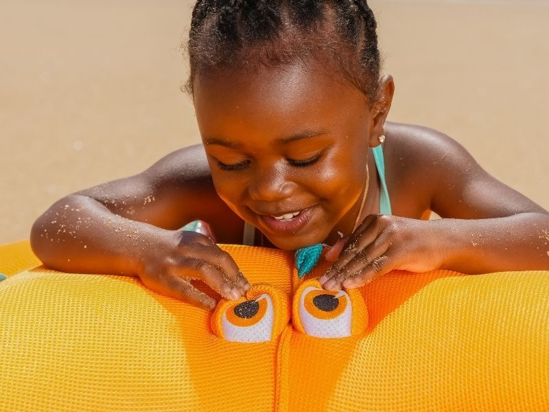little girl playing on float on beach